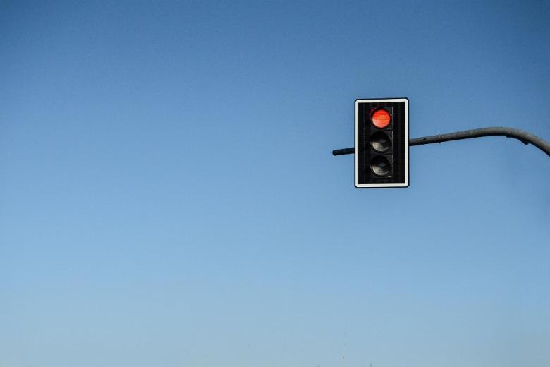Światła drogowe na rle niebieskiego nieba. Pali się światło czerwone