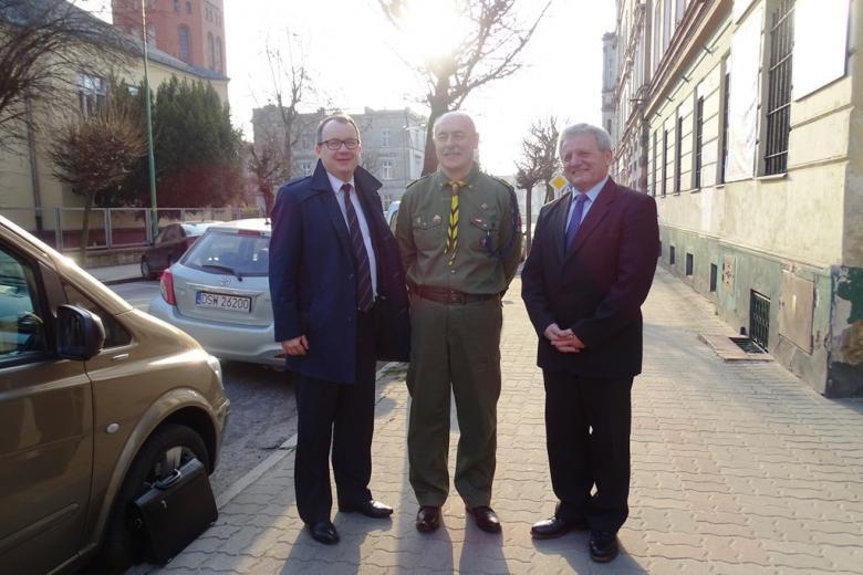 Trzej mężczyźni na ulicy, jeden  w mundurze harcerskim