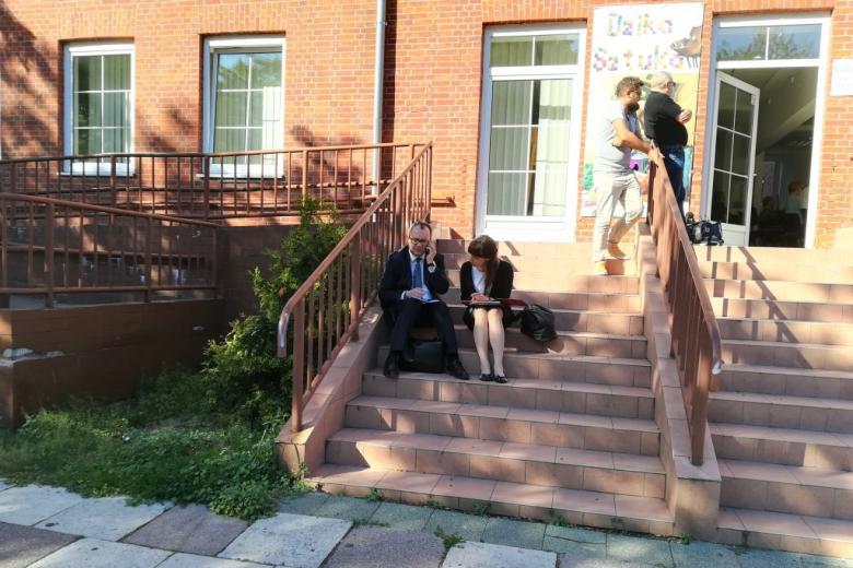 Kobieta i mężczyzna siedzą na schodkach prowadzących do galerii