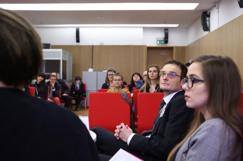 Uczestnicy patrzą na prezentację (niewidoczną w kadrze), czerwone krzesła