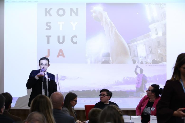 Zebrani oglądają prezentacje, na ekranie plakat z napisem KonsTYtucJA