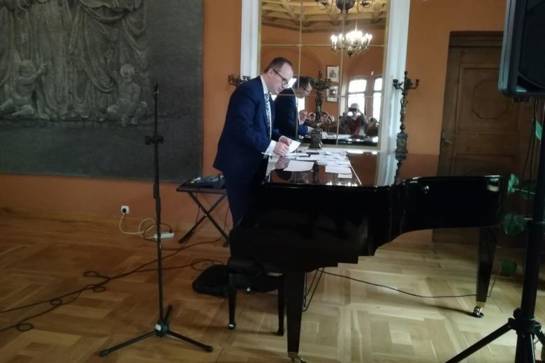 Mężczyzna rozkłada karteczki z pytaniami na klapie fortepianu w sali muzealnej