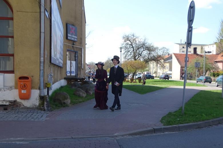 Dwoje młodych ludzi w XIX-wiecznych strojach idzie ulicą