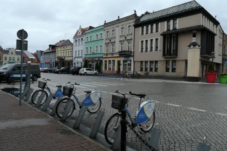 Stojak rowerów miejskich na rynku z piętrowymi kamieniczkami