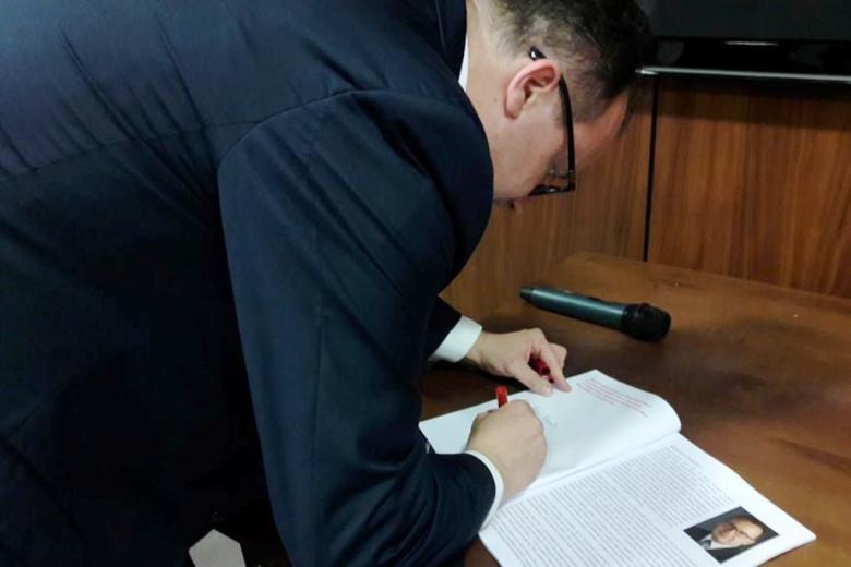 Mężczyzna podpisuje broszurę