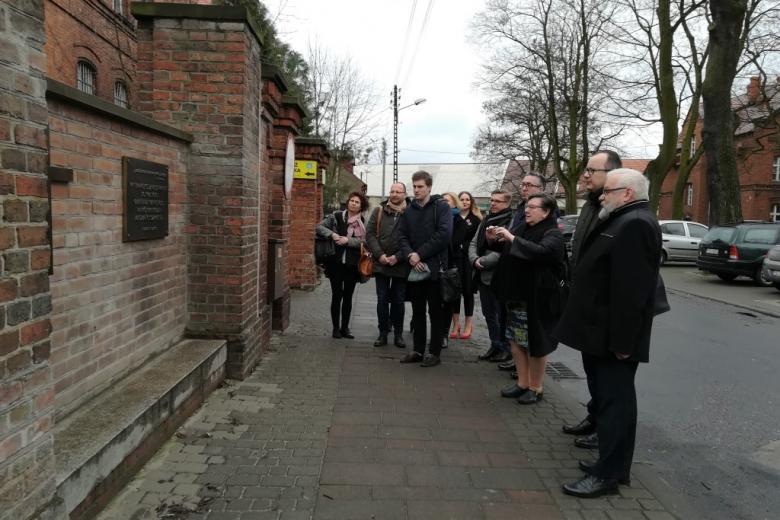 Ludzie przed murem, na którym jest tablica