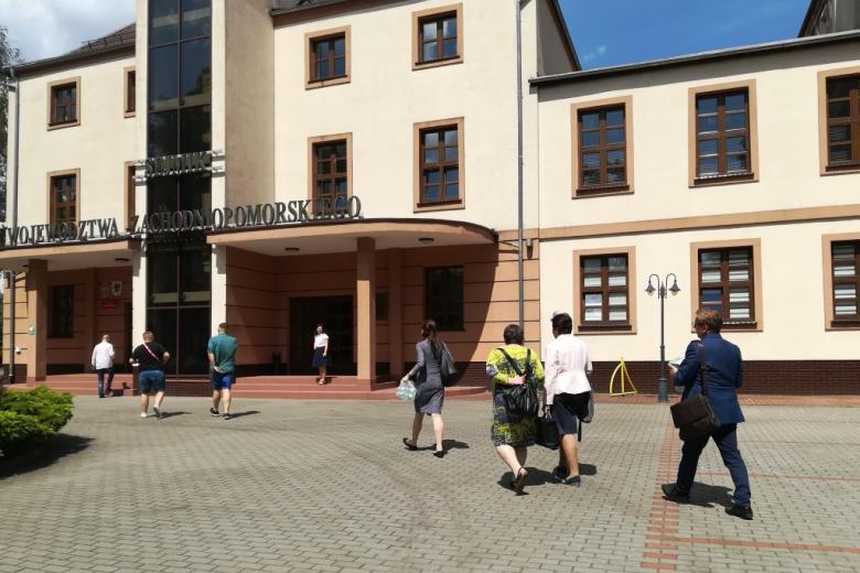 Ludzie wchodzą do budynku z naapisem Urząd Marszałkowski