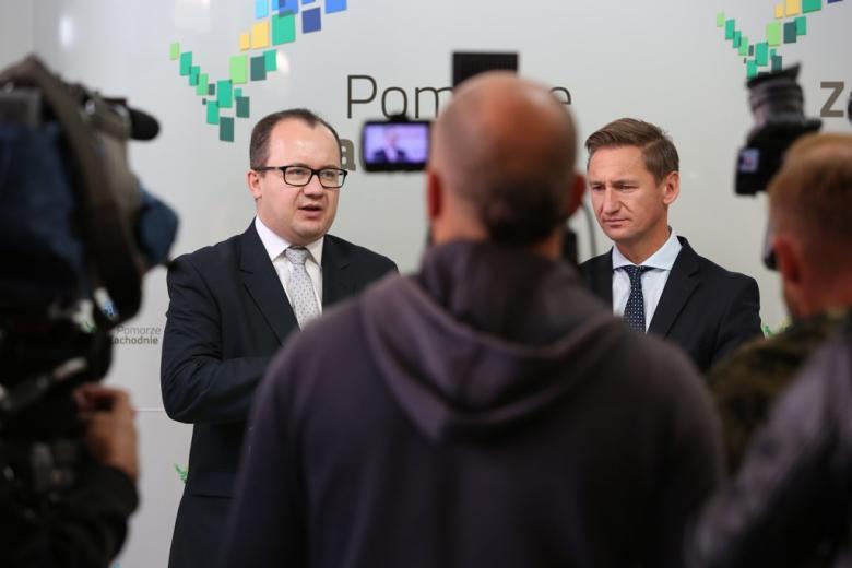 Dwaj mężczyźni wśród dziennikarzy