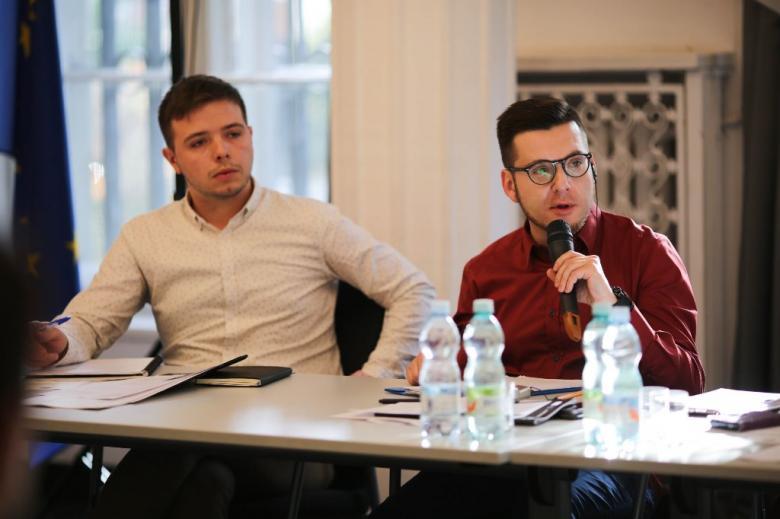 Dwaj młodzi mężczyźni przy stole, jeden mówi do mikrofonu