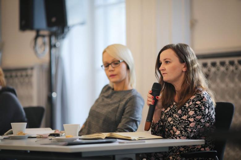 Dwie młode kobiety, jedna mówi do mikrofonu
