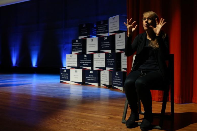 Kobieta gestykuluje na scenie
