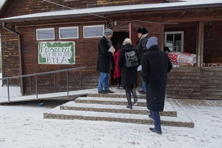 Zima. Ludzie wchodzą do drewnianego budynku na wsi