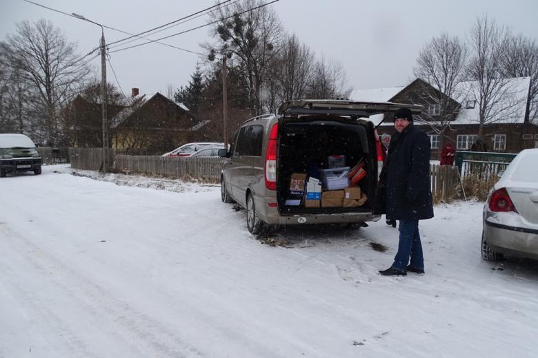 Bus przed wiejskim domem w zimowym krajobeazie. W otwartym bagażniku widać pudła