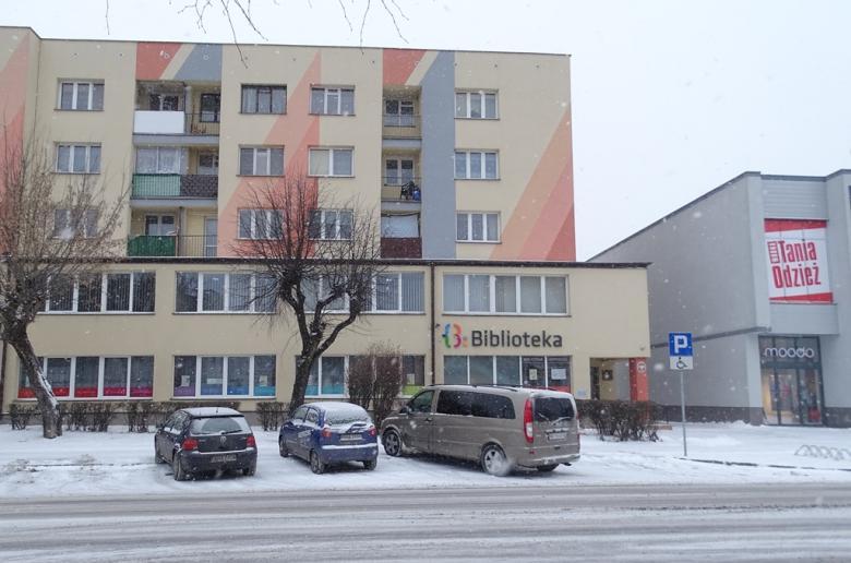 """Blok mieszkalny, nad wejściem napis """"Biblioteka"""""""
