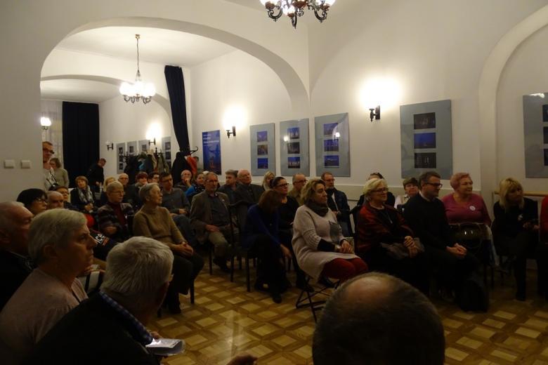 Zdjęcie: ludzie siedzą z zabytkowej sali i słuchają