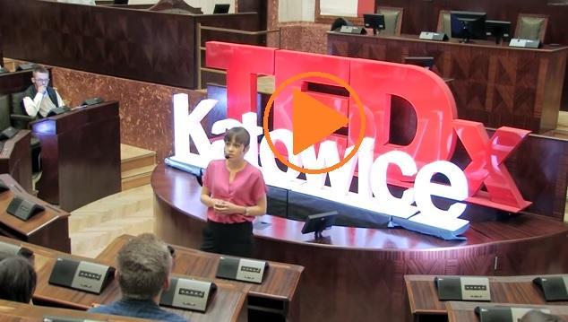 zdjęcie: kobieta w różowej bluzce przemawia na dużej sali, za nią napis TEDxKatowice