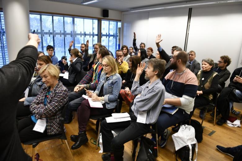 Ludzie na sali warsztatowej podnoszą ręce