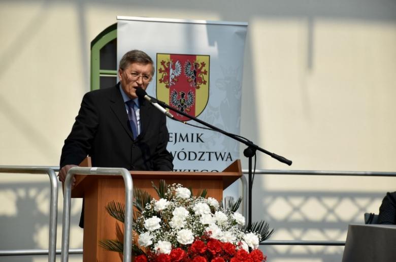 zdjęcie: mężczyzna w garniturze stoi przy mównicy, przed nią biało-czerwone kwiaty