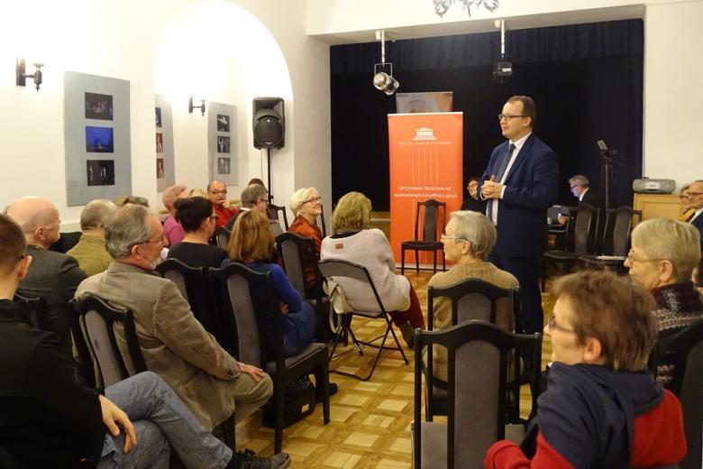 Zdjęcie: ludzie siedzą w zabytkowej sali, mężczyzna stoi
