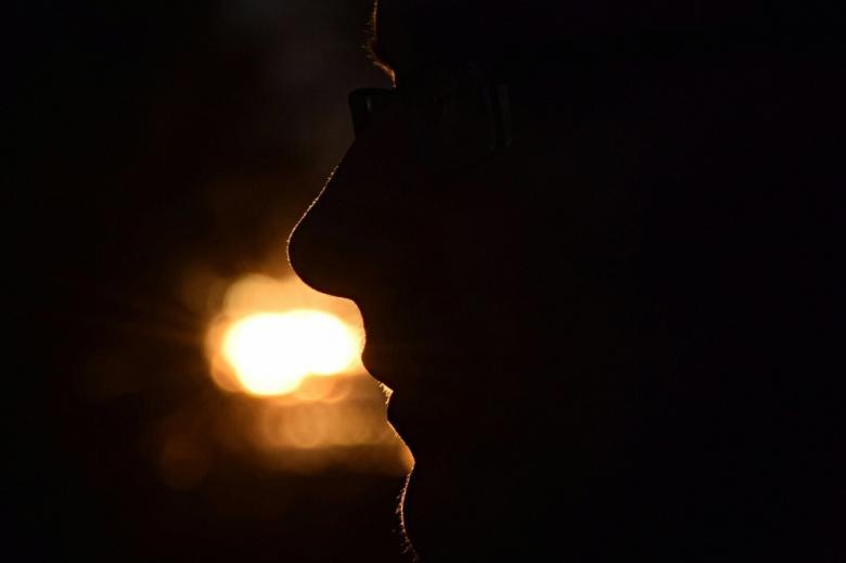 Twarz człowieka w ciemności, światło w oddali