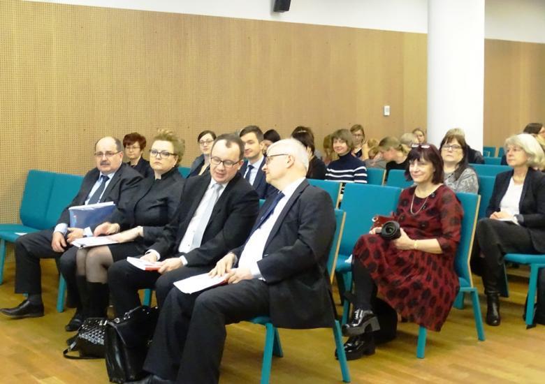 Zdjęcie: widok na salę, uczestnicy siedzą na seledynowych krzesłach