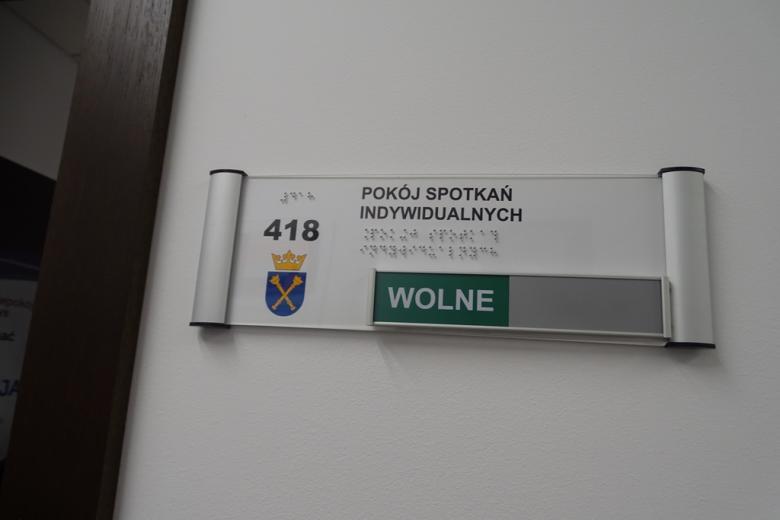 Zdjęcie drzwi: napis literami i alfabetem Braille'a