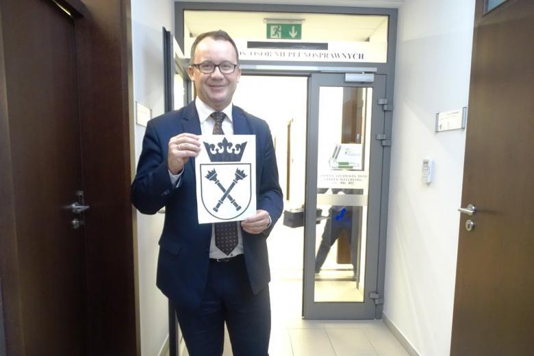 Zdjęcie: mężczyzna z herbem UJ n kartce