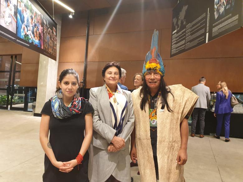 dwie kobiety i jeden mężczynzna w pióropuszu indiańskim