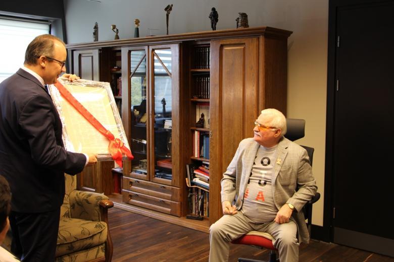 Dwaj mężczyźni: jeden unosi się na krześle, kiedy drugi wręcza mu przepasaną wstążką publikację oprawioną w ramę