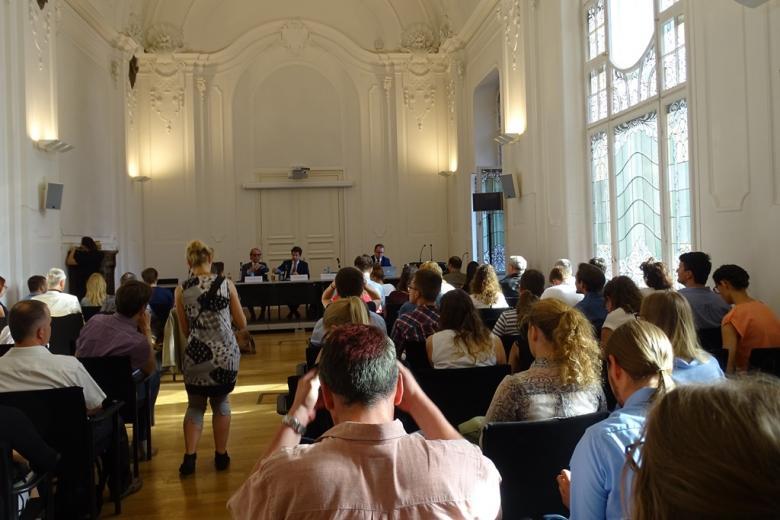 Zdjęcie: secesyjna sala pełna młodych ludzi. W głębi - stół, przy którym siedzą mężczyźni - paneliści