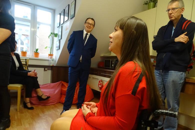Kobieta w czerwieni rozmawia z mężczyzną
