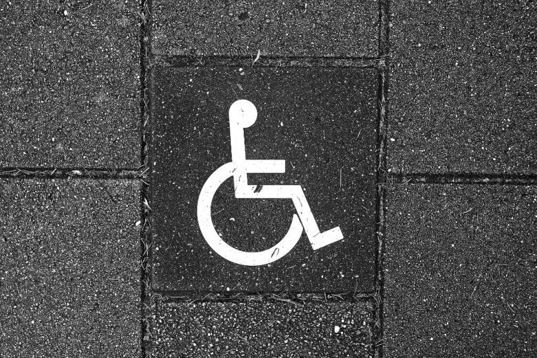 Znak pierwszeństwa dla osoby z niepełnosprawnością na szarym chodniku