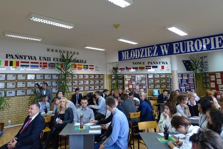 """Zdjęcie: młodzi ludzie przy stolikach w sali bibliotecznej piszą na kartkach. Na ścianie napis """"Młodzież w Europie"""" i lista krajów członkowskich UE"""