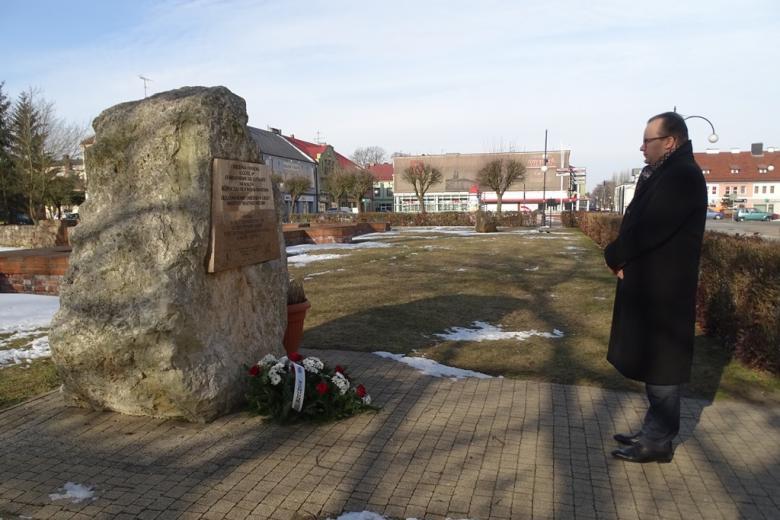 Mężczyzna stoi przed pomnikiem, przed którym leżą kwiaty, krajobraz zimowy