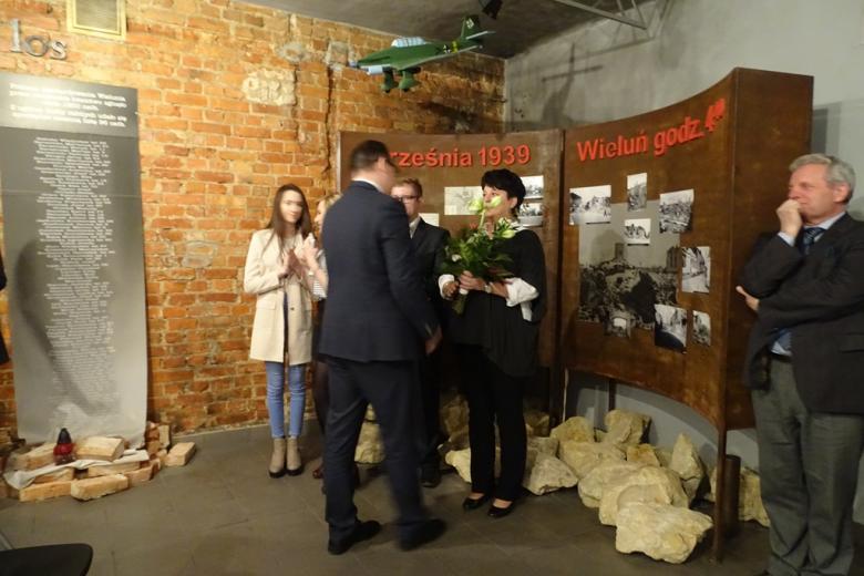 Uczniowie, nauczycielka z bukietem kwiatów i mężczyzna na tle wystawy ze zdjęciami