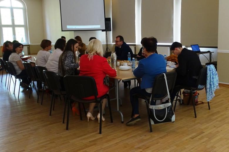 Ludzie siedzą przy stole w dużej sali