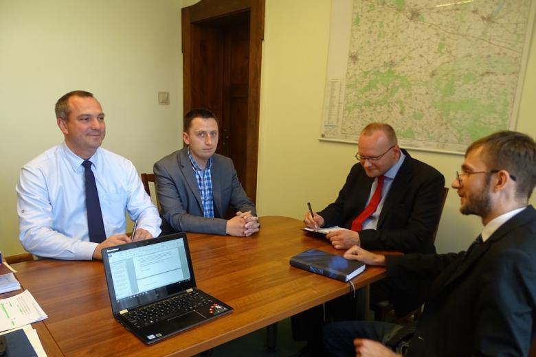 Czterej mężczyźni przy stole w urzędzie