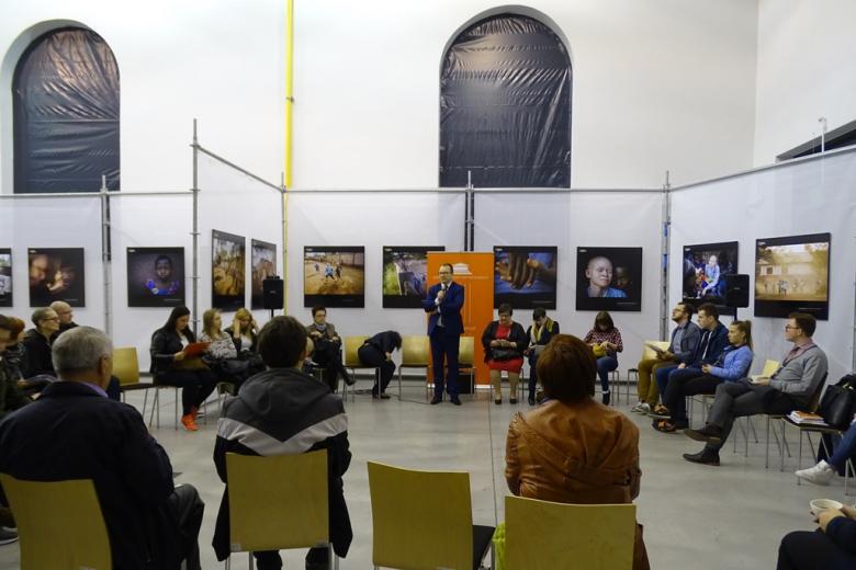 Przemysłowe wnętrze, na ścianach - duże kolorowe fotogragie, ludzie siedzą w kręgu