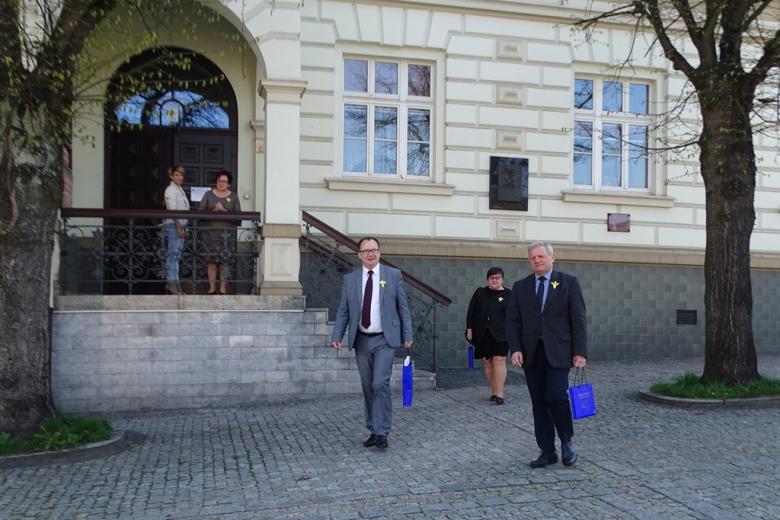 Mężczyźni i kobieta wychodzą z budynku żegnani przez grupę osób na wysokim ganku. Wszyscy mają w klapach żółte kwiaty