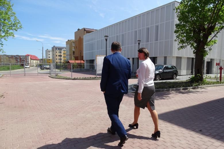 Mężczyzna i kobieta idą w stronę nowoczesnego budynku