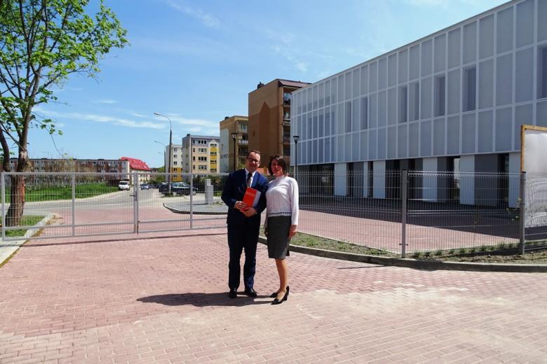 Mężczyzna i kobieta pozują do zdjęcia przed nowoczesnym budynkiem