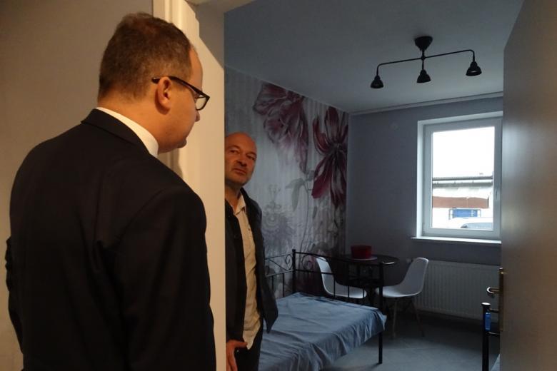 Zdjęcie: dwaj męzczyxni na progu pięknie umeblowanego pokoju