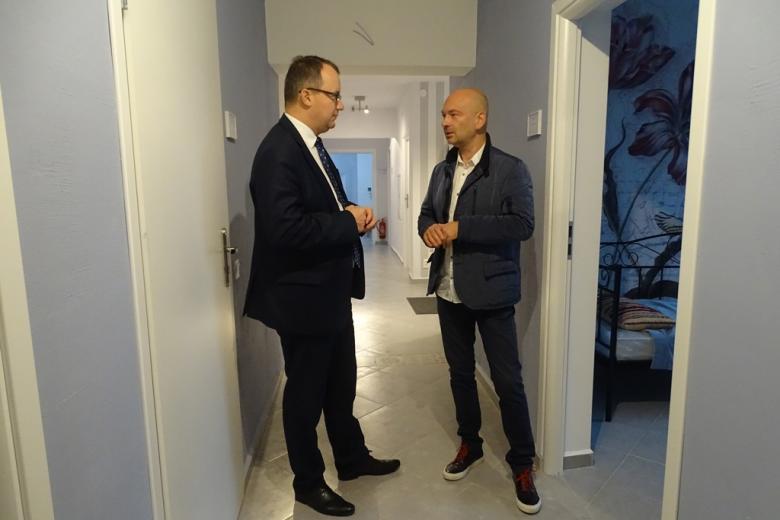 Zdjęcie: dwaj mężczyźni rozmawiają na jasnym korytarzu