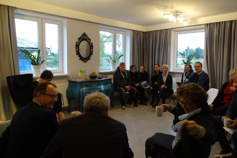 Zdjęcie: ludzie siedzą w pięknej sali, na ścianie - lustro w rzeźbionej ramie