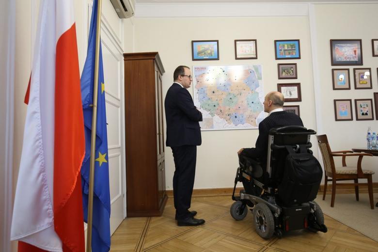 Mężczyzna na wózku i męzczyzna stojący przed mapą polski w gabinecie, gdzie w rogu stoją flagi Polski i Unii