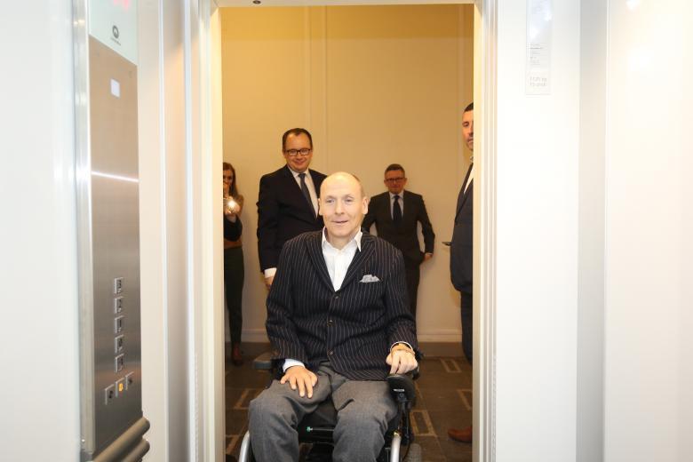 Mężczyzna na wózku wjeżdza do windy