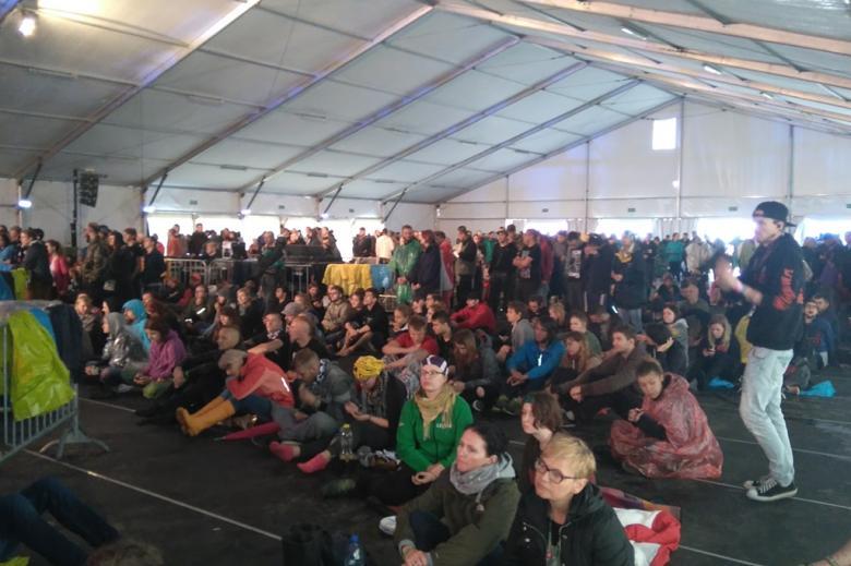 Zdjęcie: młodzi ludzie siedzą na ziemi i słuchają debaty