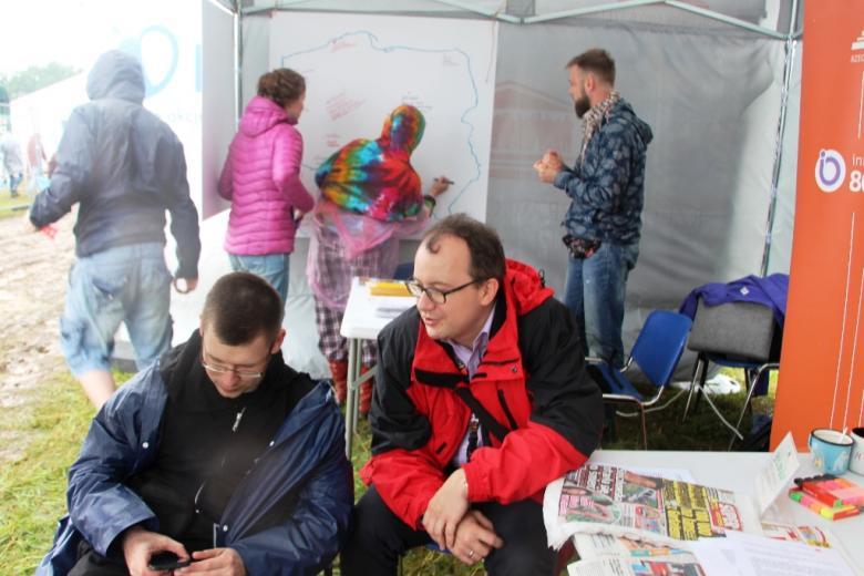 zdjęcie: ludzie w namiocie, na pierwszym planie dwaj mężczyźni siedzą