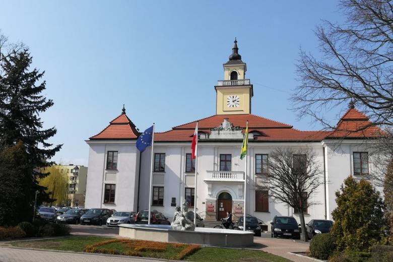 Ratusz z trzema masztami, na których wiszą flagi Polski, Unii Europejskiej i Ostrowi