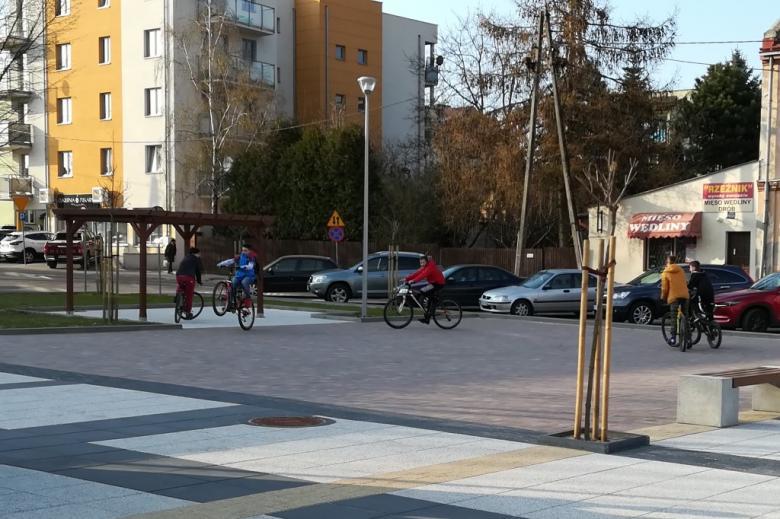Młodzi ludzie ćwiczą akrobacje rowerowe na placyku